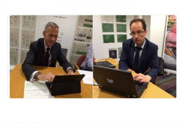 Nigel Gibbens and Javier Dominguez on their laptops answering questions on AMR on Twitter