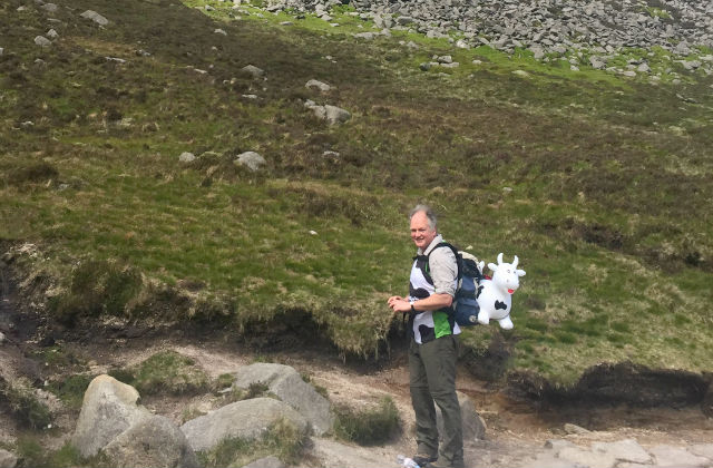 Robert Huey Chief Veterinary Officer Northern Island, pictured with inflatable cow about to start hiking up the mountain.