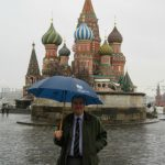 Photo of Chris Teale in front of St Basil's Cathedral in Moscow holding an umbrella