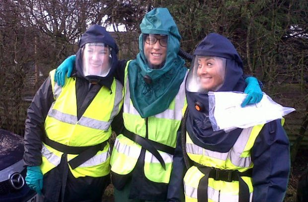 Photo of 3 APHA vets in biohazard suits and hi-visibility vests