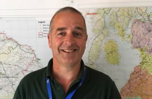 Photo of Iain Bell, APHA Veterinary Adviser in the Field Epidemiology Team, in front of some maps of Scotland