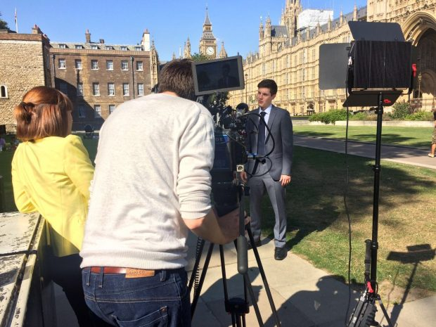 Anthony being interviewed in front of the houses of parliament by a cameraman and an interviewer.