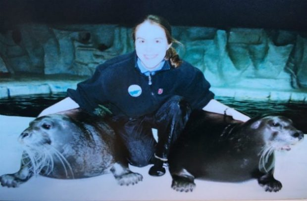 Caroline Conradi with two seals next to water
