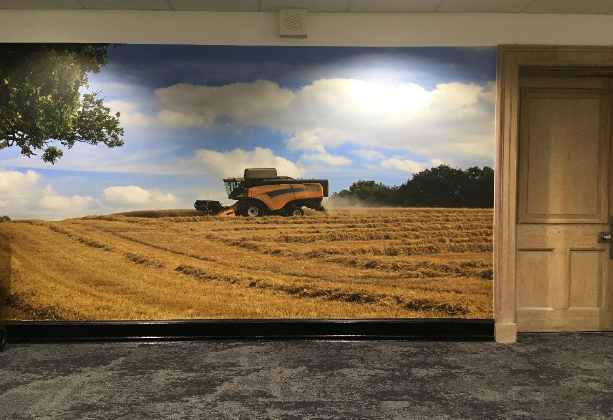 An image of a combine harvester mural on a wall with a door on the left
