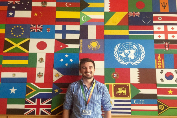 Daniel standing in front of a large number of flags from different countries