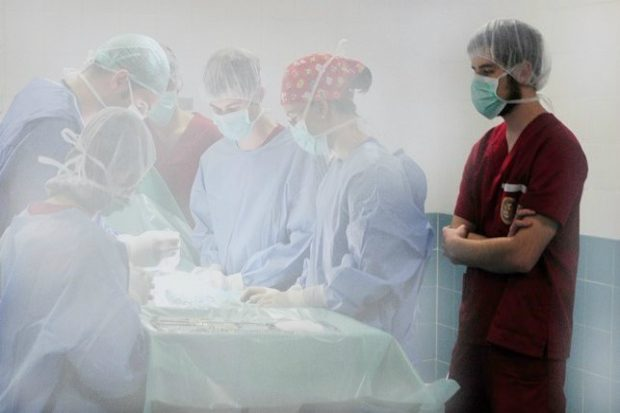 Francisco standing in an operating theatre in scrubs observing an operation