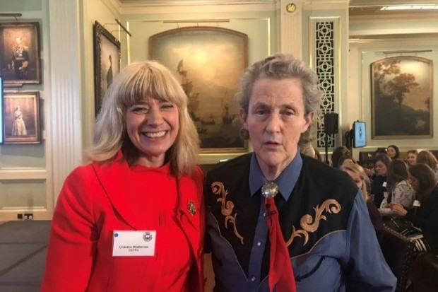 Christine standing in a room with Temple Grandin